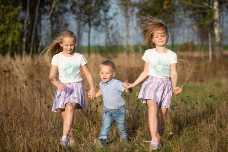 Happy family: sisters and little brother on a summer meadow.