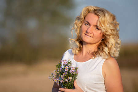 Beautiful middle-aged blonde with a bouquet of wildflowers. Stock fotó