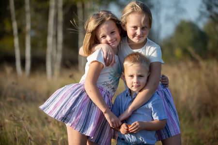 Little brother and two sisters are looking at the camera.