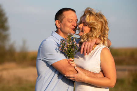 Beautiful middle-aged couple in love hugging on the background of nature.