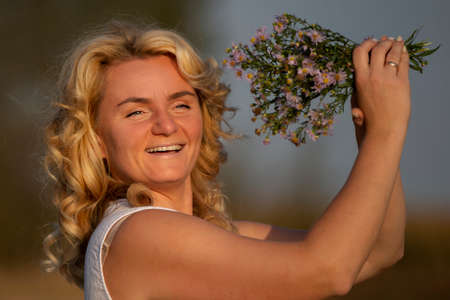 Beautiful middle-aged blonde with a bouquet of wildflowers with a smile.
