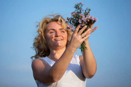 Beautiful middle-aged blonde with a bouquet of wildflowers against the blue sky.