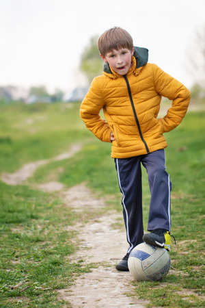 A boy in nature stands with a soccer ball.