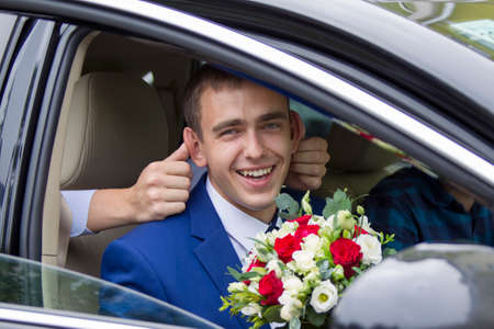 Cheerful groom sitting in the car laughing cheerfully. Merry groom. The bridegroom will go to the bride. Groom funny Stock Photo
