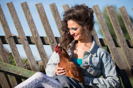 A beautiful young woman in a denim jacket with bright makeup sits with a chicken on the background of an old fence.