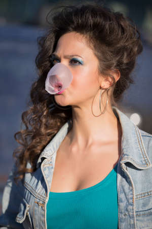 A beautiful young woman in a denim jacket inflates the gum.