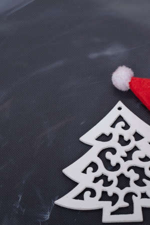 Wooden toy tree and red santa claus hat on a black background. Christmas background.