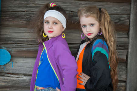 Little girls in bright clothes with makeup on their faces on a wooden background. A child in the style of the nineties.