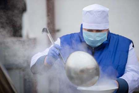 Cooking street food during the coronavirus panademy. A chef in a medical mask with a large scoop pours soup.