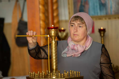 A Russian woman in a headscarf lights a candle in the church.