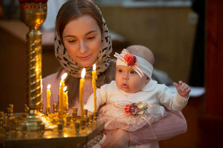 Mother and child in a church by candlelight. Woman with a baby in the temple.