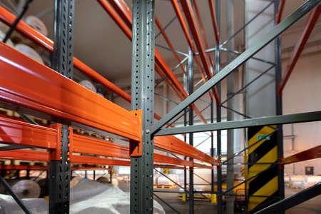 Warehouse premises of a factory or workshop with metal shelves. Foto de archivo