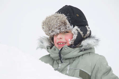 The boy in a hat with earflaps in a snowdrift