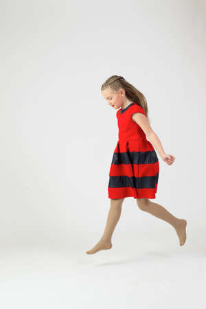 Little blonde in red dress running Stock Photo