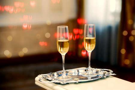 Two glasses of champagne against a background of bokeh spots. Festive romantic background. Foto de archivo