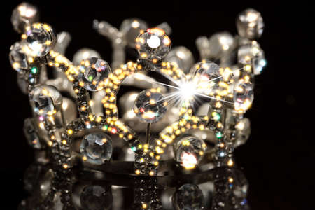 Gold crown with shiny stones on a black background. Standard-Bild