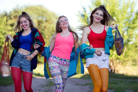 Three beautiful country girls dressed in the style of the nineties are walking along the road.