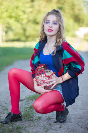 A beautiful 90s country girl in bright clothes holds a string bag with a can of birch sap. Russian Woman in the style of the 90s.