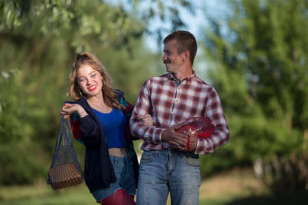 Forgettable village couple, a girl and a man in a plaid shirt, carry bread and juice.