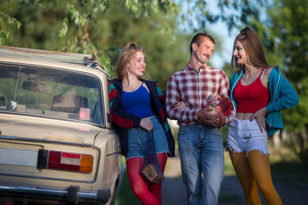 Handsome girls and a country man dressed in 90s style stand near an old car. Standard-Bild