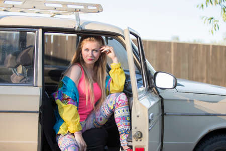 Beautiful girls in the style of the 90s sits in an old car.