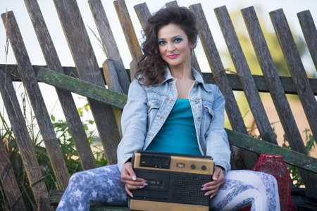 A beautiful country girl in bright clothes sits on a wooden bench with a cassette recorder. Woman in the style of the 90s. Standard-Bild