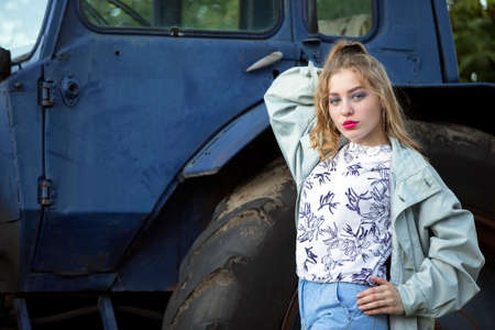 A beautiful country girl in the style of the 90s in bright clothes stands near a tractor. Standard-Bild