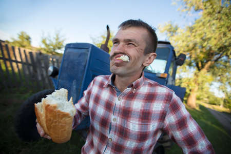 The village man tractor driver is hungry and is eating a loaf.
