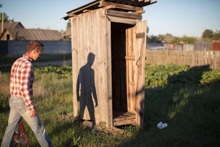 The man goes to the rustic wooden toilet.