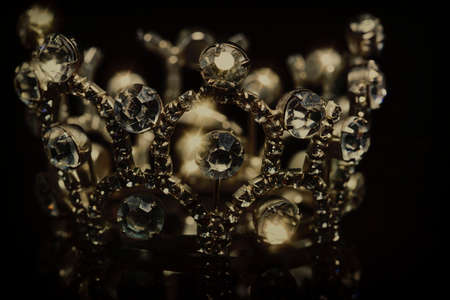 Gold crown with shiny stones on a black background.