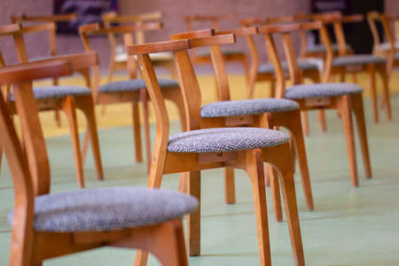 Group of chairs in an empty room spaced with a distance Standard-Bild