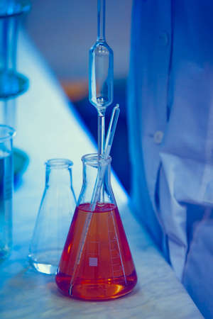 Vaccine production laboratory. Glass flasks with a chemical liquid in infrared radiation.