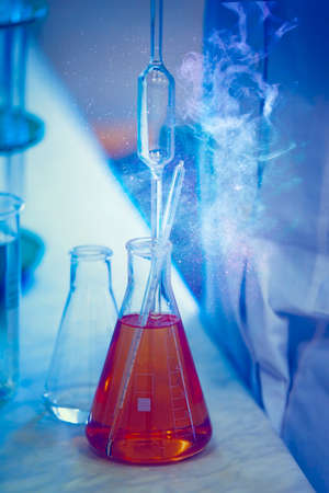 Glass laboratory flasks with chemical substance and magic glow. Making a magic potion. Standard-Bild