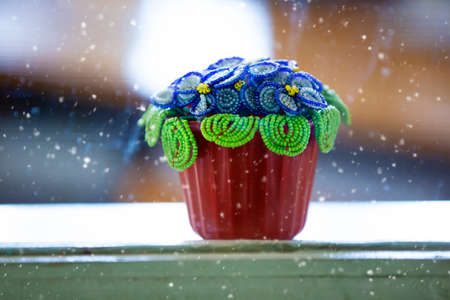 A beaded flower in a pot stands on the windowsill.