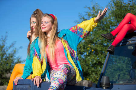 Beautiful country girls dressed in the style of the nineties sit on a tractor. Standard-Bild