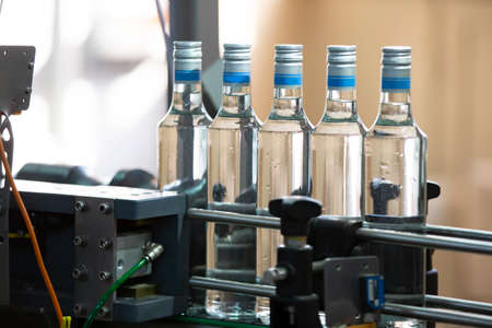 A long row of glass bottles on a conveyor belt. Production of alcoholic beverages.
