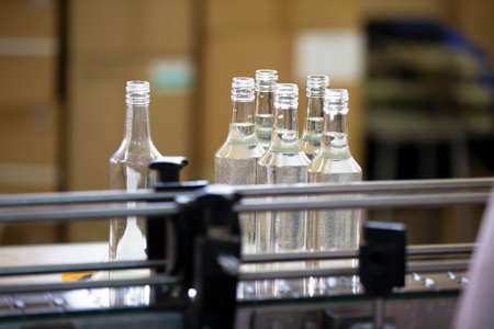 A row of glass bottles on a conveyor belt for the production of alcoholic beverages.