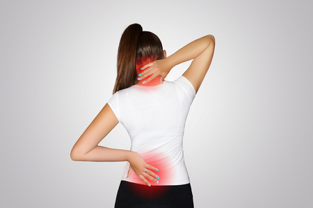 Pain in the neck and back. A young woman suffers from pain in the neck and back. Spine osteoporosis. Scoliosis. The place of pain indicated by a red spot. Concept of health.