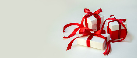 Christmas Gift's in White Box with Red Ribbon on Light Background. New Year Holiday Composition Banner. Copy Space For Your Text Foto de archivo