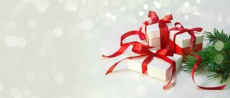 Christmas Gifts in White Box with Red Ribbon on Light Background. New Year Holiday Composition Banner. Copy Space For Your Text