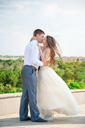 Beautiful Bride in White Dress kissing with Groom.