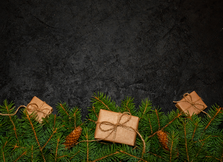Minimal Holiday Composition From Green Fir Branches with Small Gift Boxes on Dark Background. Creative Nature Concept. Flat Lay. Copy Space For Your Text