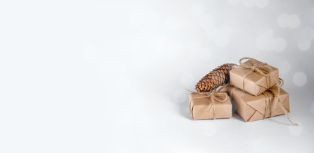 Christmas Gifts with fir cone on Light Background. Minimal New Year Holiday Composition. Copy Space For Your Text