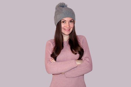 Young Beautiful Woman in Sweater and Knitted Hat on Grey Background. Winter Concept