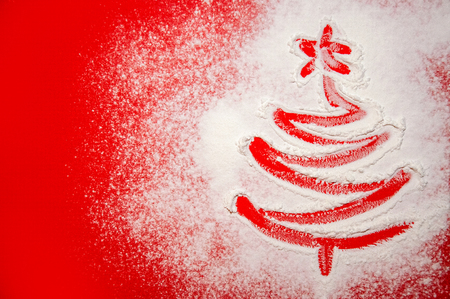 Christmas Tree Drawn on the Scattered Flour on Red Background. Minimal Holiday Concept 写真素材