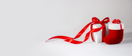 Christmas Gift in White Box with Red Ribbon and Toy Sock on Light Background. New Year Composition Banner. Copy Space 写真素材