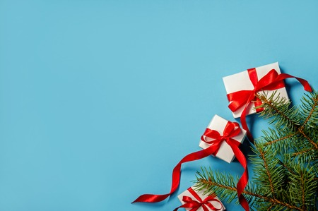 Christmas Gifts White Box with Red Ribbon on Blue Background Fir Tree Branches on Blue Background Flat Lay Copy Space