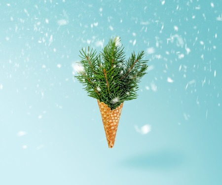 Christmas Tree Ice Cream Cone Levitation in Snow on Ligth Blue Background. New Year Concept. Minimal Holiday Composition 写真素材