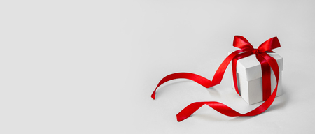 Christmas Gift in White Box with Red Ribbon on Light Background. Minimal New Year Holiday Composition Banner. Copy Space.