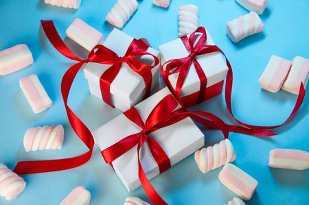 Christmas Holiday Composition. New Year Gift White Boxes Red Ribbon with Marshmallows on Blue Background. Flat Lay.